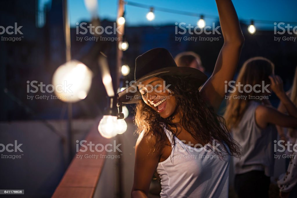 Cheerful woman dancing during terrace party stock photo