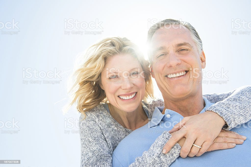 Cheerful Woman Embracing Man From Behind Against Sky stock photo