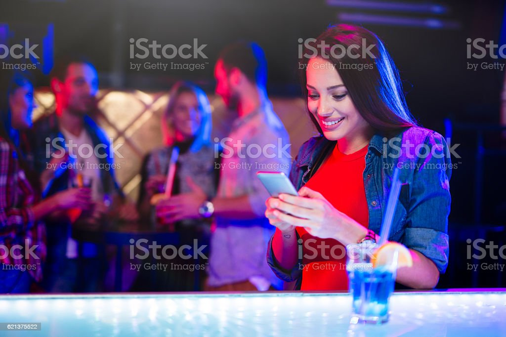 Cheerful woman having cocktail while text messaging in nightclub stock photo