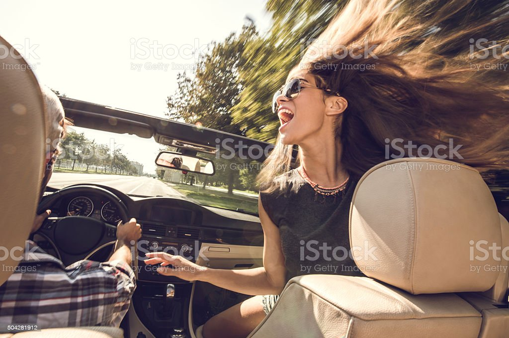 Cheerful woman having fun in cabriolet with her boyfriend. stock photo