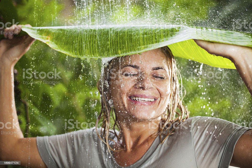 Cheerful woman having fun in jungle during tropical rain royalty-free stock photo