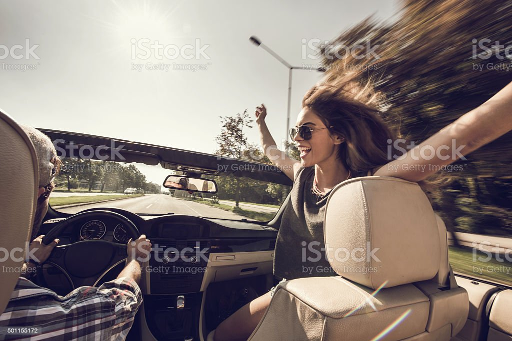 Cheerful woman having fun while driving in cabriolet. stock photo
