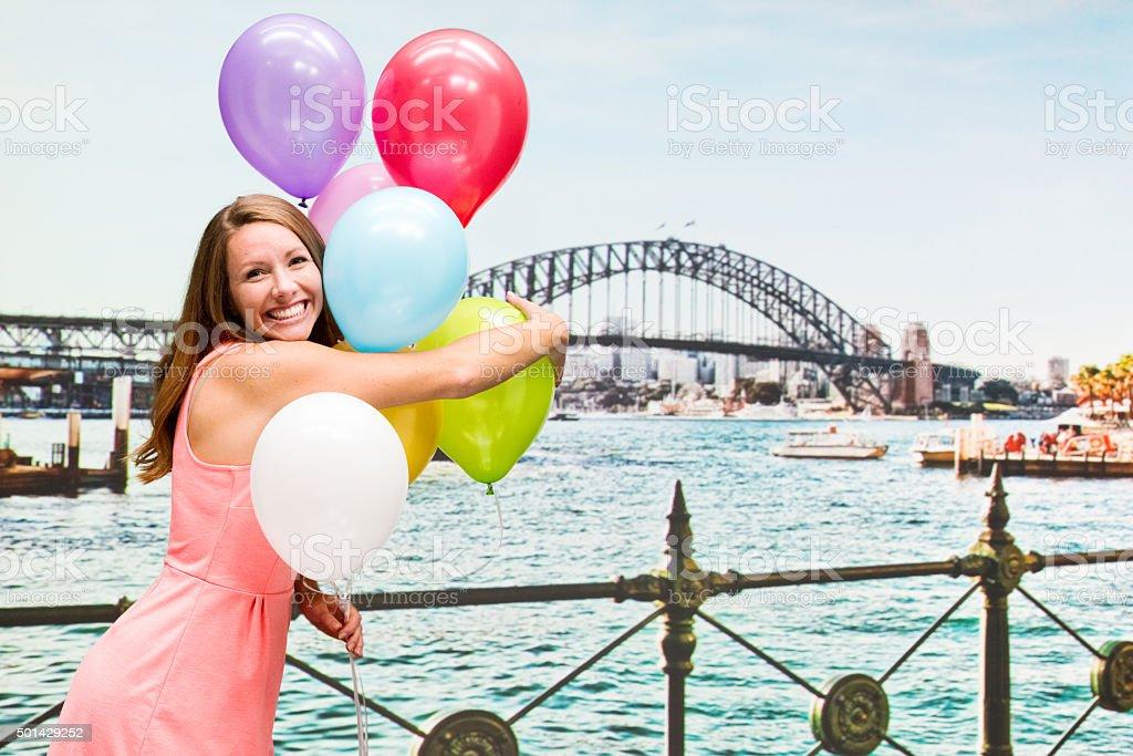 Cheerful woman holding balloon outdoors stock photo