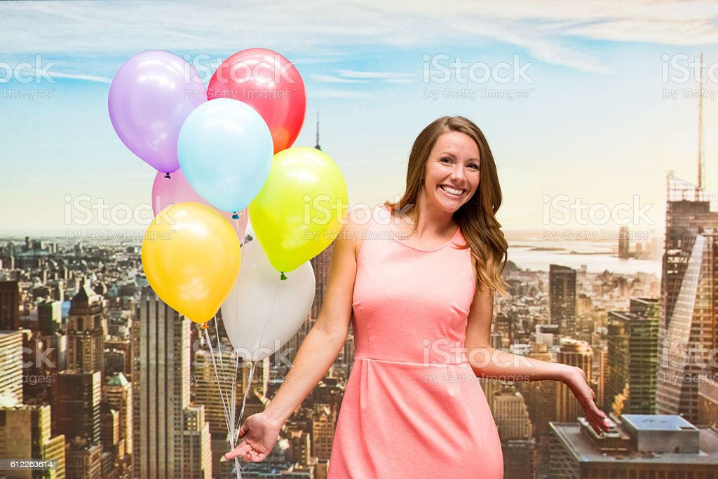 Cheerful woman holding balloons and presenting stock photo