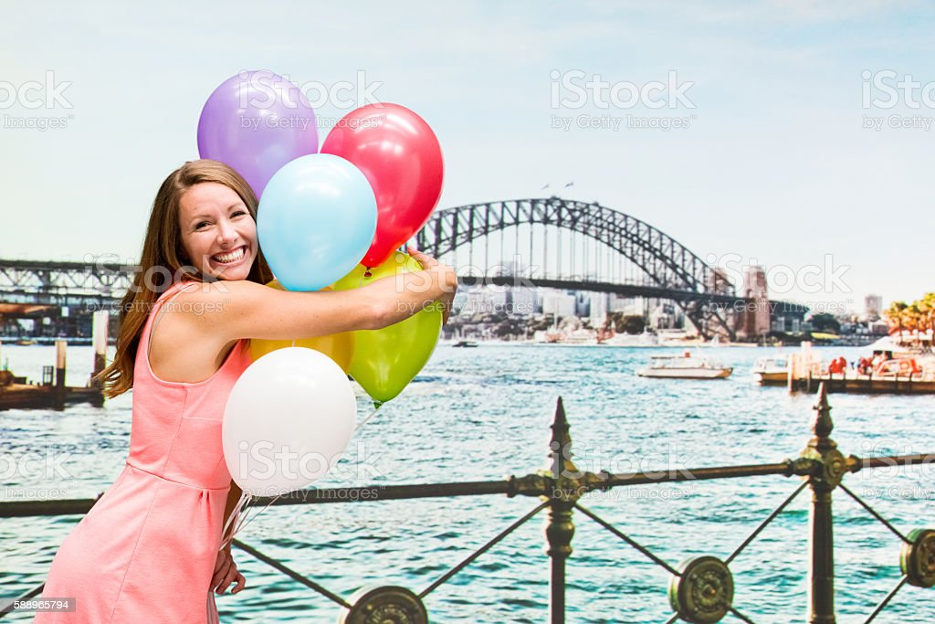 Cheerful woman holding balloons outdoors stock photo