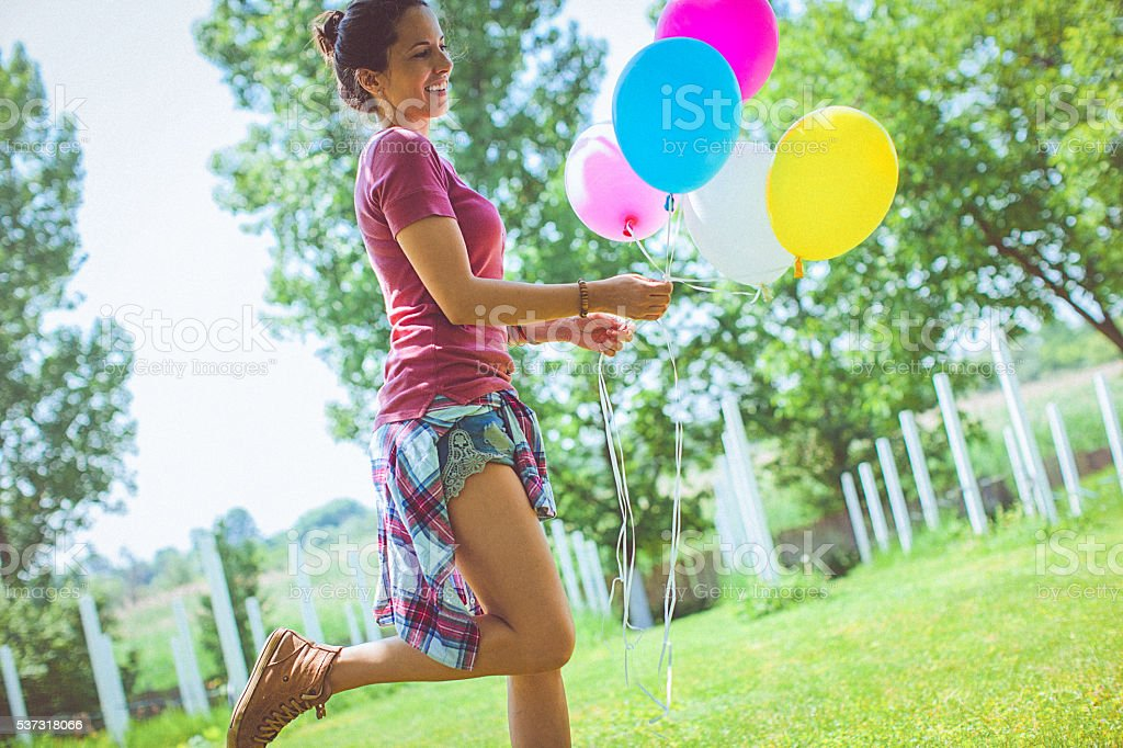 Cheerful woman holding colorful balloons, runs through the park stock photo