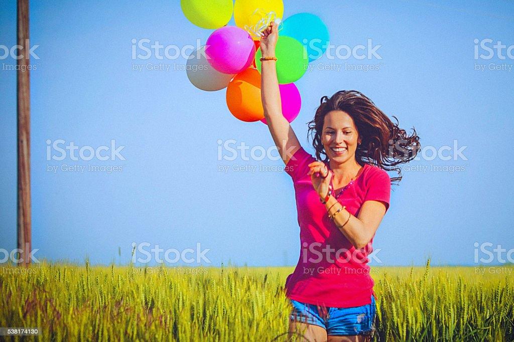 Cheerful woman holding colorful balloons, runs through wheat field stock photo