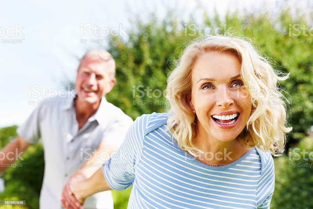 Cheerful woman holding hand of a senior man against sky stock photo