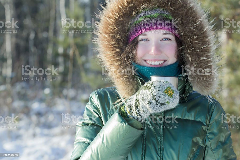 Cheerful woman holding stainless steel thermos flask tourist cup stock photo
