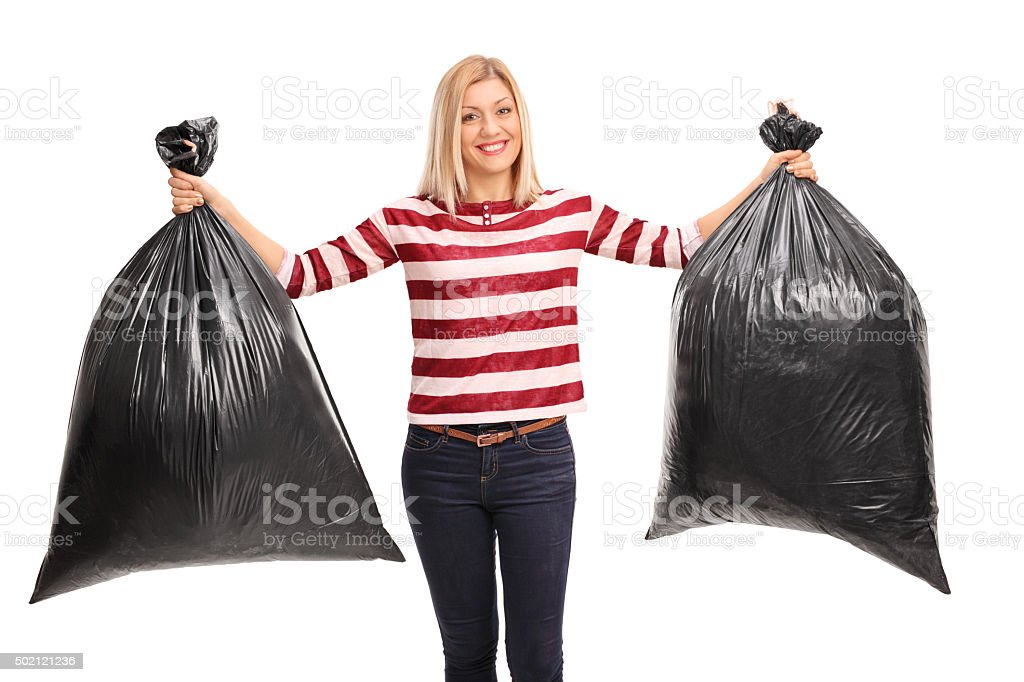 Cheerful woman holding two trash bags stock photo