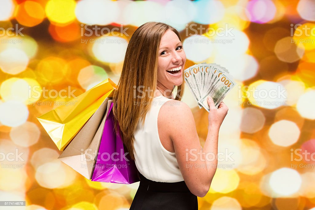 Cheerful woman holding us currency stock photo