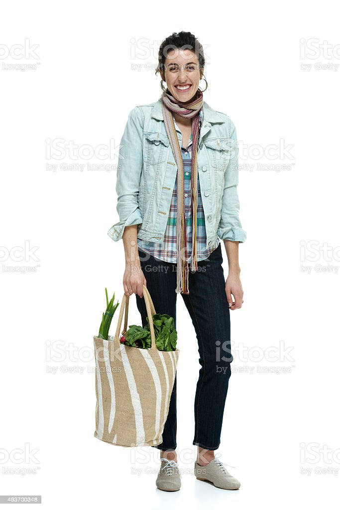 Cheerful woman holding vegetable bag stock photo