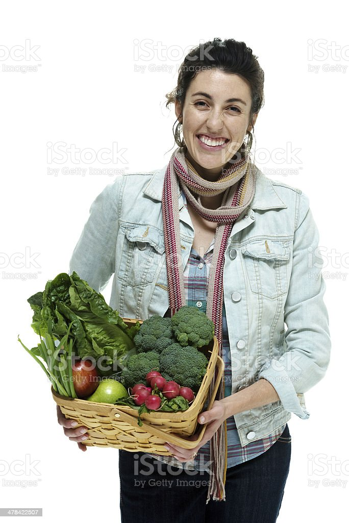 Cheerful woman holding vegetable basket stock photo