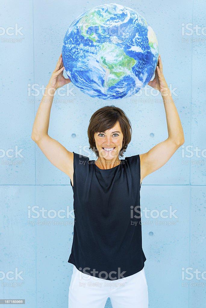 Cheerful woman holding world globe royalty-free stock photo