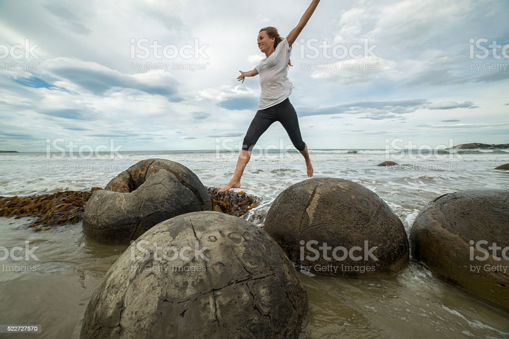 Cheerful woman jumps from boulder to boulder stock photo