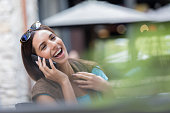 Cheerful woman laughs while talking on smart phone