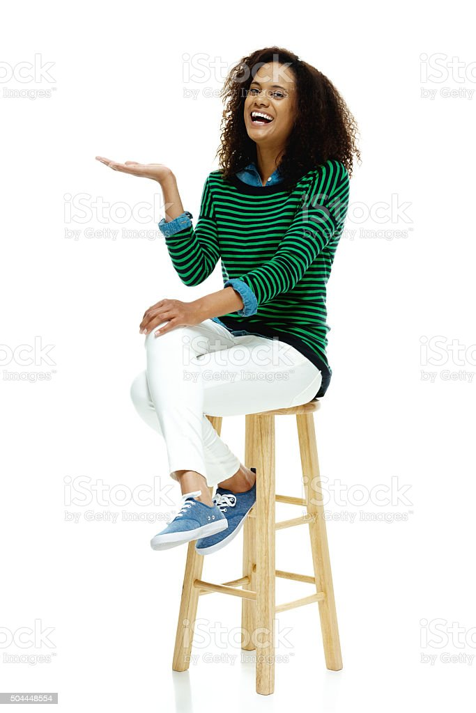 Cheerful woman on stool and presenting stock photo