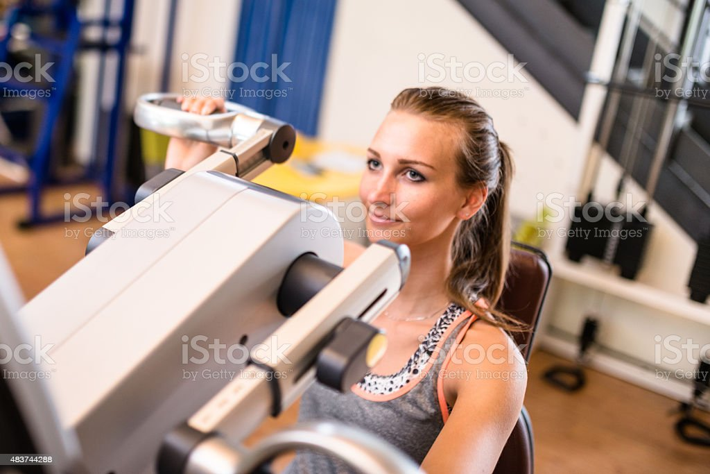 cheerful woman on the machine in the gym stock photo