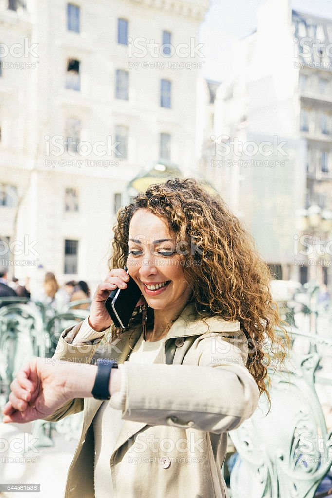 Cheerful woman on the phone checking time outside subway station stock photo