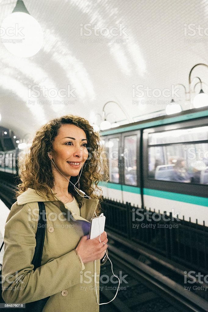 Cheerful woman on the phone, subway train on background stock photo