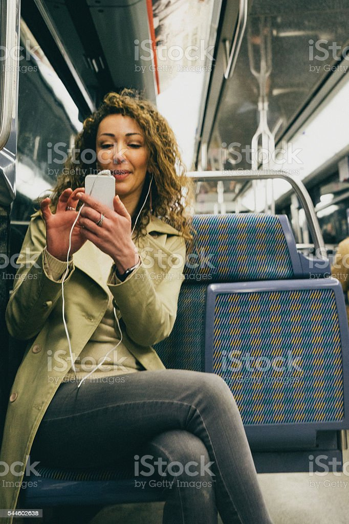 Cheerful woman on the phone travelling in the subway train stock photo