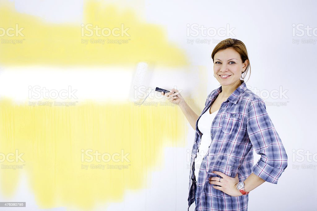 Cheerful woman painting a wall. royalty-free stock photo