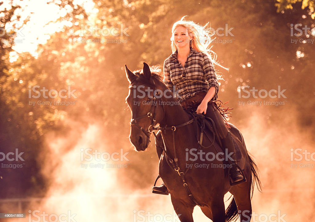 Cheerful woman practicing with her horse at sunset. stock photo