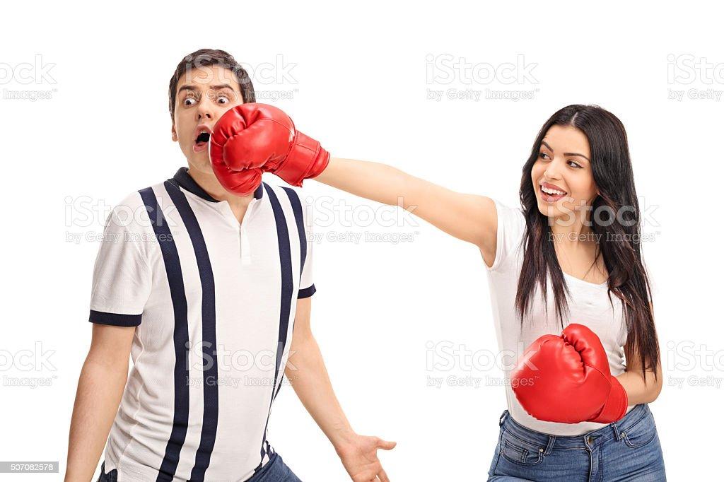 Cheerful woman punching her boyfriend stock photo