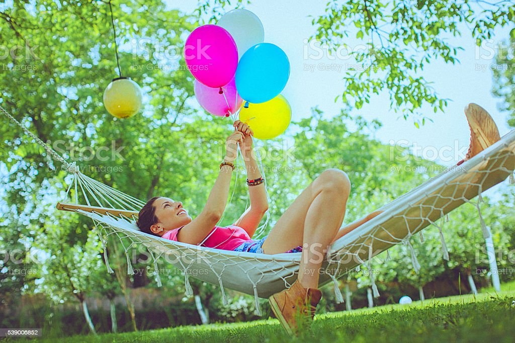 Cheerful woman relaxing in a hammock in the garden stock photo