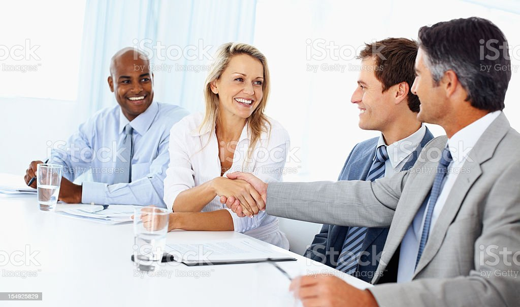 Cheerful woman setting a deal with male executive royalty-free stock photo