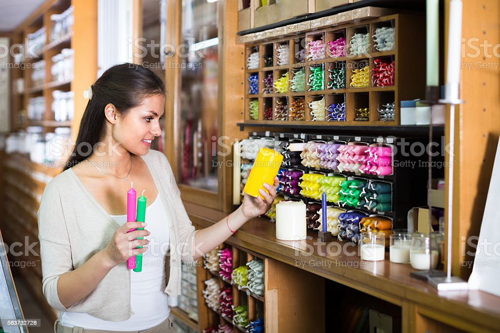 Cheerful woman shopping multicolored candles stock photo