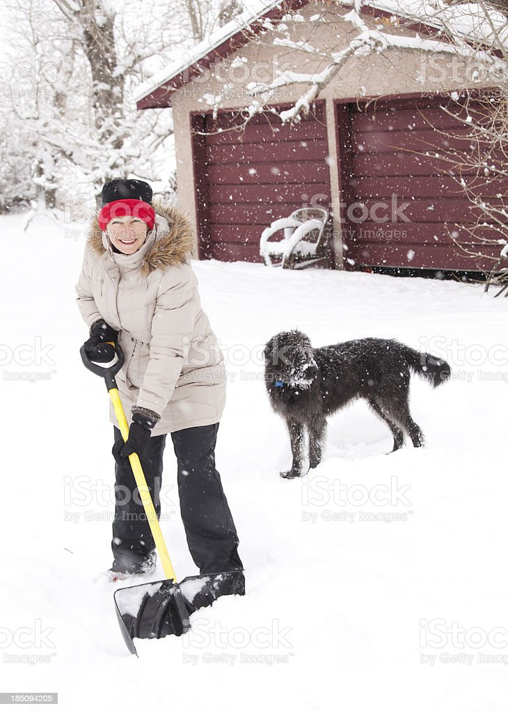 Cheerful woman shovelling snow in blizzard stock photo