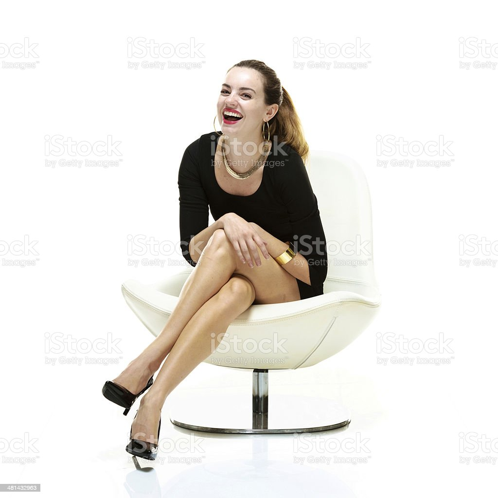 Cheerful woman sitting on chair & looking at camera stock photo