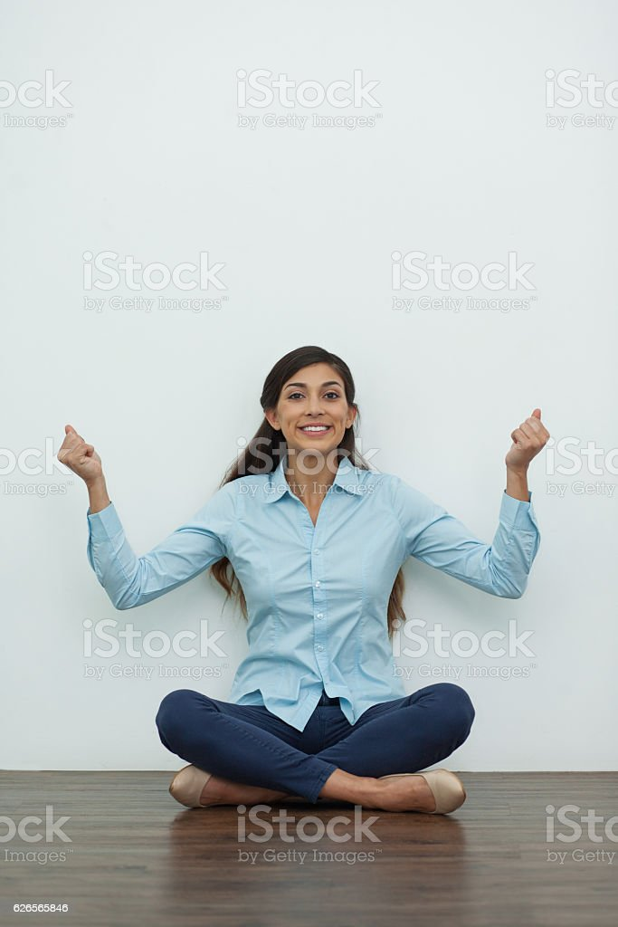 Cheerful Woman Sitting on Floor and Pumping Fists stock photo