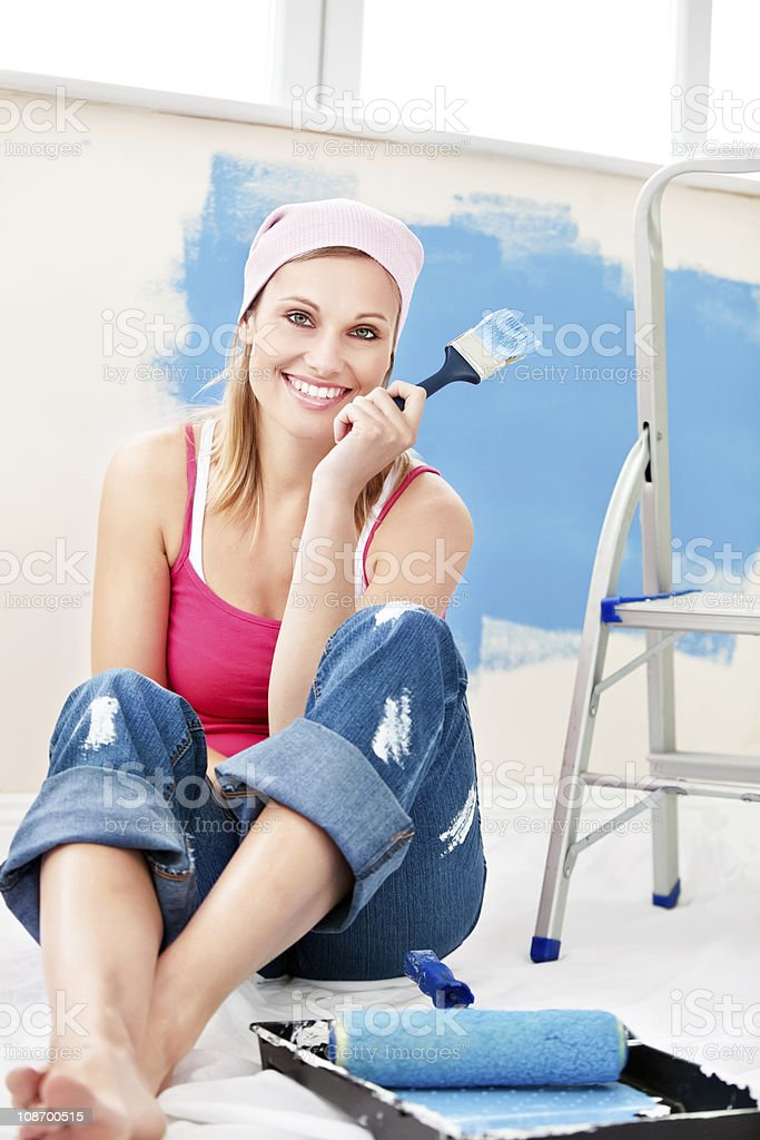 Cheerful woman sitting on the floor after painting a room royalty-free stock photo
