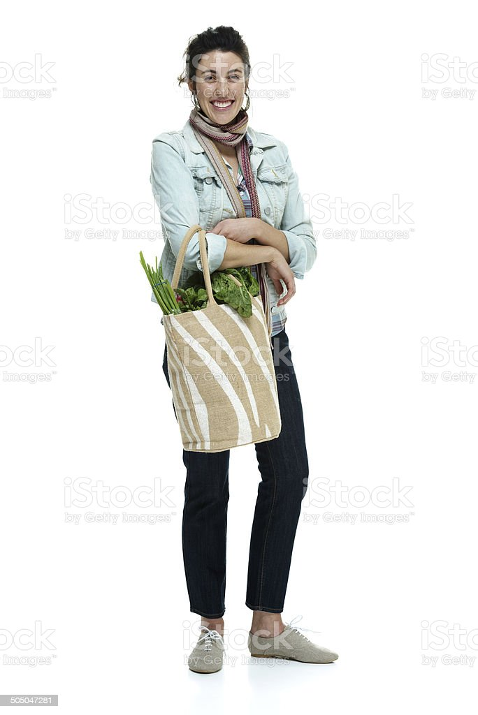 Cheerful woman standing and holding bag of vegetables royalty-free stock photo