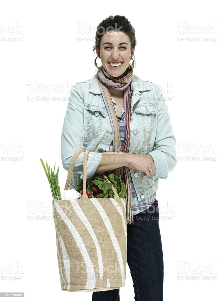 Cheerful woman standing with vegetables bag royalty-free stock photo