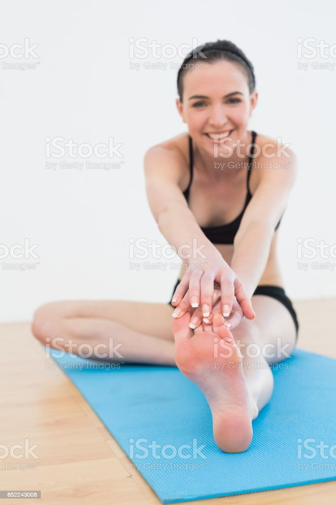 Cheerful woman stretching leg in fitness center stock photo