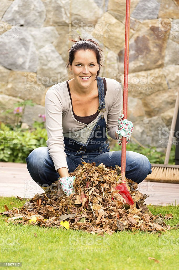 Cheerful woman sweeping leaves autumn pile backyard stock photo
