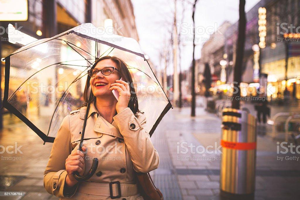 Cheerful woman talking on smartphone stock photo