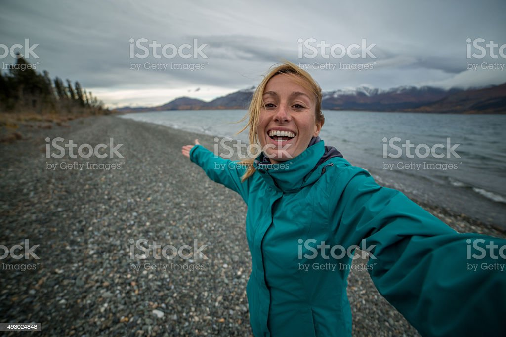 Cheerful woman traveling in Canada takes selfie portrait near lake stock photo