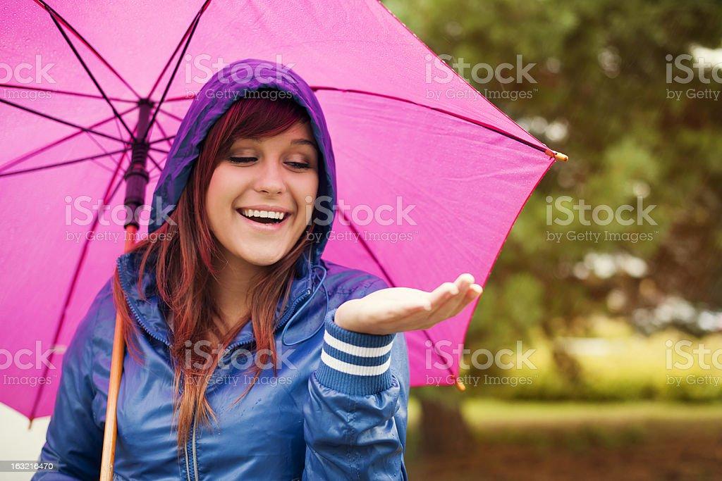 Cheerful woman under pink umbrella checking for rain stock photo
