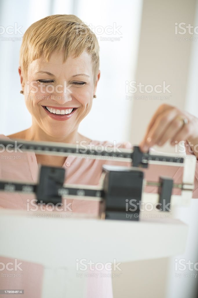 Cheerful Woman Using Balance Weight Scale stock photo