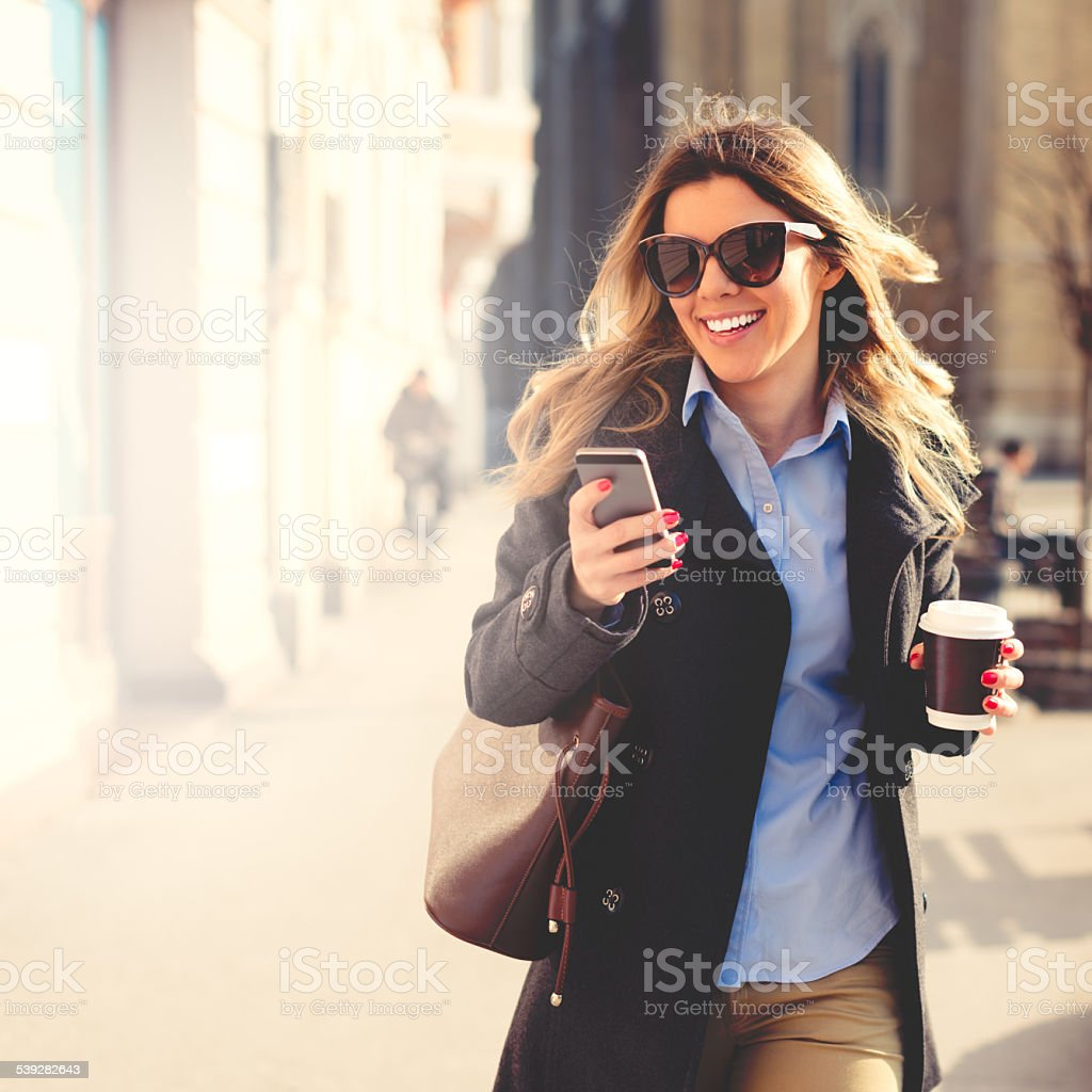 Cheerful woman using smart phone stock photo