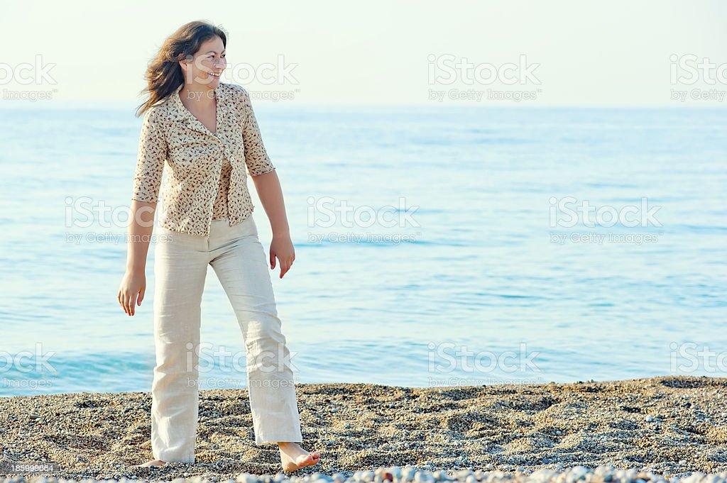 cheerful woman walking along the beach barefoot royalty-free stock photo