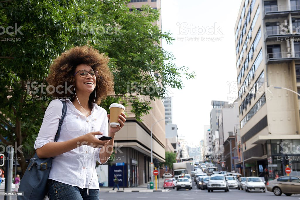 Cheerful woman walking in the city with cell phone stock photo