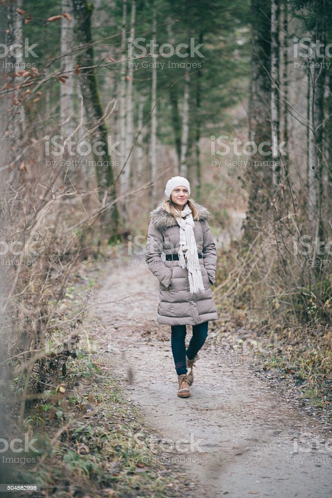 Cheerful woman walking in woods in cloudy winter day stock photo