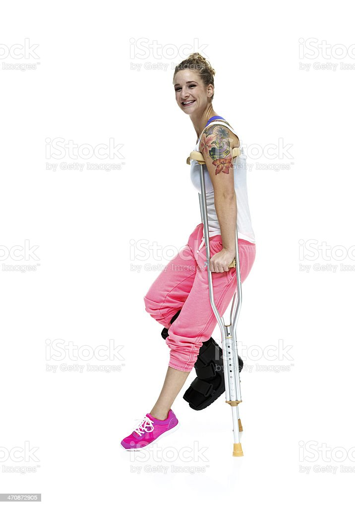 Cheerful woman walking with crutches royalty-free stock photo