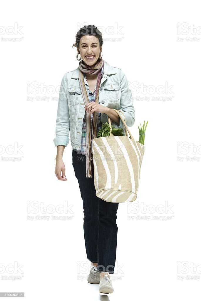 Cheerful woman walking with vegetable bag stock photo