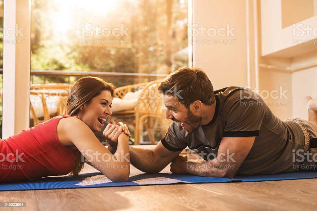 Cheerful woman winning in arm wrestling with her boyfriend. stock photo